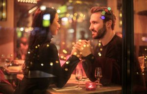 healthy loving couple holding hands under romantic lights
